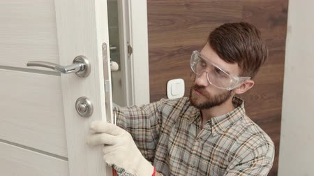 schroef : Young handyman in uniform fixing door lock.