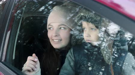 samochód : Mom and son are sitting in the car and looking through the window at the winter forest