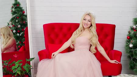 クラウン : A blond woman in a beautiful dress and a crown is posing in the studio. Red sofa 動画素材