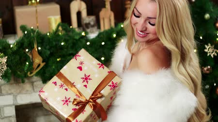 подарок : A blond woman looking at a beautiful christmas present.