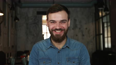 złamanie : Portrait of a young man with a beard in a cafe. Blue shirt. Smile