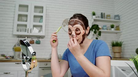 zeller : girl put on cosmetic mask eats celery at mirror in kitchen