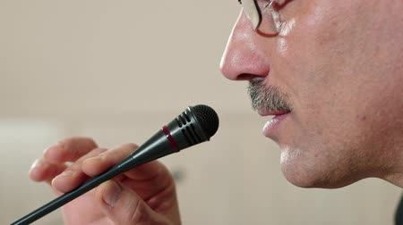 kopogás : Speaker checks the microphone before speaking and speak, face close-up, side view.