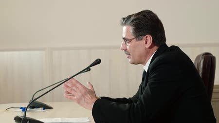 helyettes : Politician answers the questions at a press conference, side view. Stock mozgókép