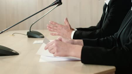 restraint : Speaker with an assistant at a press conference, hands with documents close-up, side view.