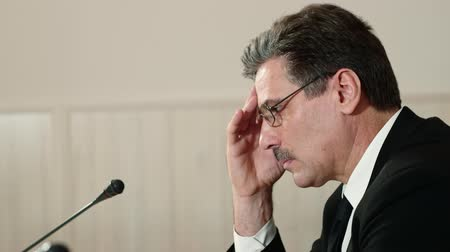 press conference : Troubled speaker attentively listens to a question from the journalist at a press conference and answers it, side view. Stock Footage