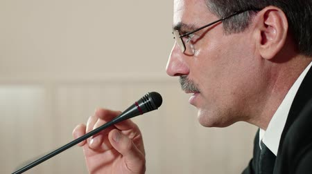 helyettes : Speaker checks the microphone before speaking and speak, face close-up, side view.