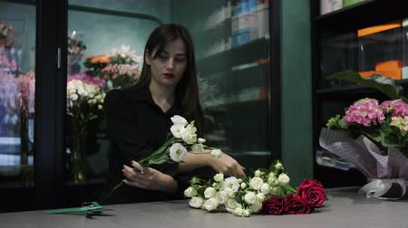 decorador : Professional woman florist cuts white and red roses with a pruner over the table in flower shop.