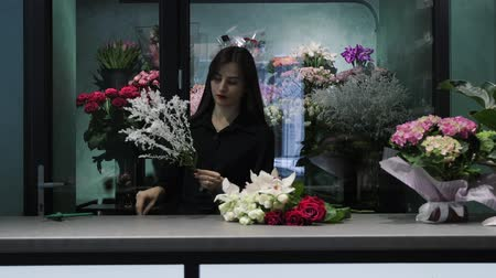 decorador : Professional woman florist prepare solidago for the bouquet with roses and orchids in floower shop. Stock Footage