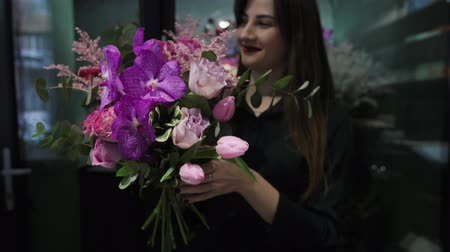 phalaenopsis : Professional woman florist makes the bouquet from pink flowers tulips, roses, orchids and solidago.