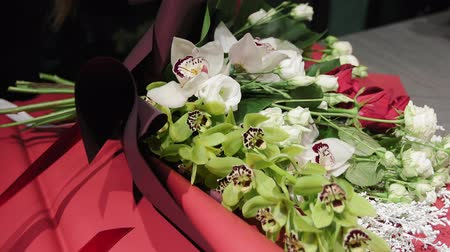 phalaenopsis : Florist ties a ribbon on a beautiful bouquet of flowers from Orchid Cymbidium, red and white roses and solidago in paper, hands close-up.