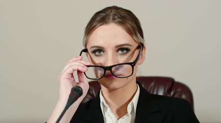 microphone : Businesswoman politician takes off and puts on glasses preparing for the speaking, front view.