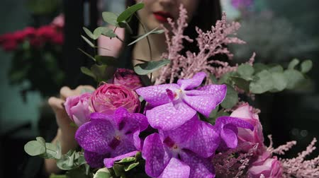 нежный : Professional woman florist makes the bouquet from pink flowers tulips, roses, orchids and solidago.