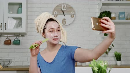 zeller : girl with facial mask makes selfie eating celery in kitchen Stock mozgókép