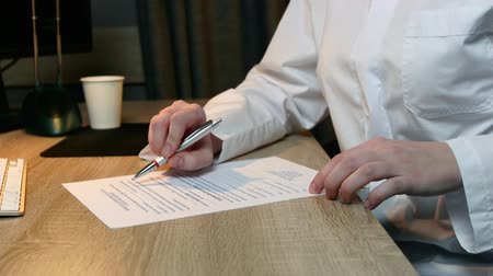 boticário : Woman scientist writes a test sitting at a table in white uniform. Hands close up.