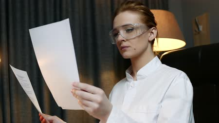 phd : Woman scientist reads the papers, carefully analyzes the data.
