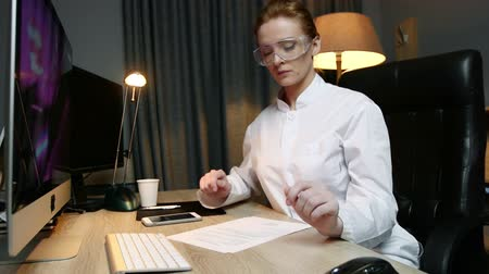 phd : Woman scientist reads the documents and types the message on phone while working in office.