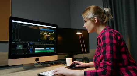 creator : Woman video editor works with footage on her computer, works in office. Video editing, side view.