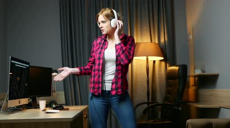 お気に入り : Young happy woman in headphones is listening music and dancing in home office, relax after work. 動画素材