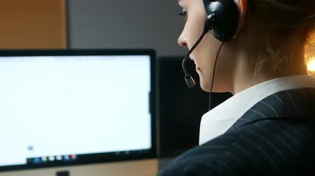 поддержка : Call center operator answers the call and communicates with the client. Back view. Стоковые видеозаписи