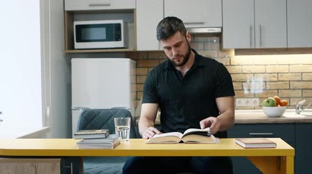 master's degree : Man reads a book sitting in the kitchen at home and drinks water.