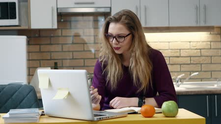grãos : Woman learns on a computer and and writes notes in notepad in the kitchen at home. Stock Footage