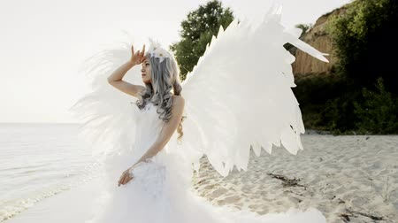 nevinný : Delicate beautiful blonde woman posing with angel wings seashore