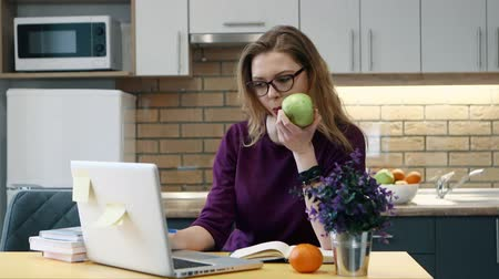 grau : Woman learns on a computer and and writes notes in notepad in the kitchen at home. Stock Footage