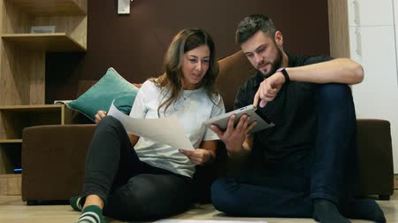mesafe : Colleagues a man and a woman discuss a joint project using a drawing and a tablet sitting on the couch in the office.