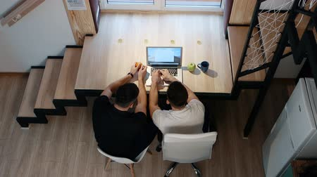 tangerina : Two male works on laptop sitting by the table Home office concept. Top view. Vídeos