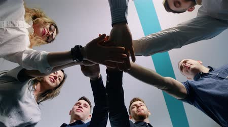 munkatárs : Successful team in office: many hands holding together standing in circle. Team building concept.