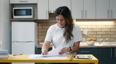 governante : Woman architect is working with papers sitting in the kitchen at home. Vídeos
