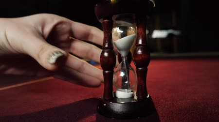 croupier : Dealer puts an hourglass on the poker table. Close-up of womans hand. Casino gamble. Stock Footage