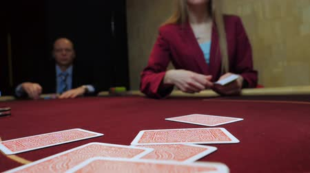 croupier : Casino gamble: Dealer deals the cards. Players bet. Cards close-up. Slow motion.