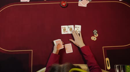 gergin : Casino dealer putting cards on red table, poker game, gambling, close-up hands. Top view. Stok Video