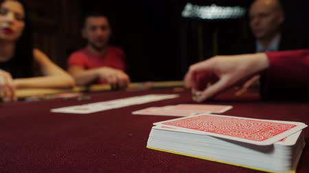 willpower : Cards on the poker table. People are playing poker on background. Casino gamble.