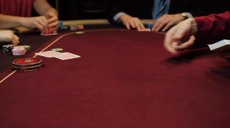 croupier : Casino gamble: Dealer deals the cards. Players bet. Cards and hands close-up.