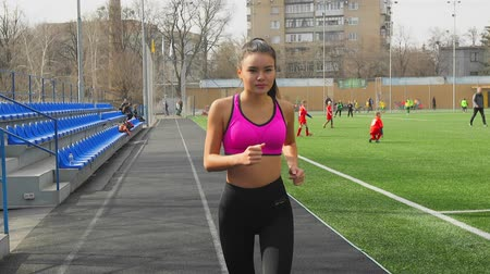 závodní dráha : Athletic asian young girl is running on stadium. Fitness, sports concept.