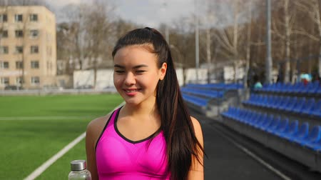 versenypálya : Asian young sporty girl with bottle of water in hands is walking on stadium after training. Stock mozgókép