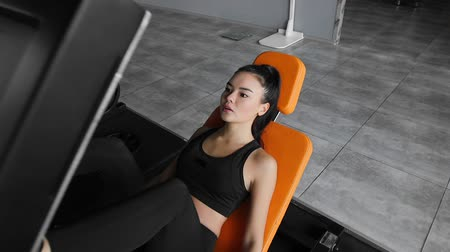 çabaları : Sporty young asian woman is working out on a simulator doing exercises for legs muscles. Sports workout in the gym indoors. Stok Video