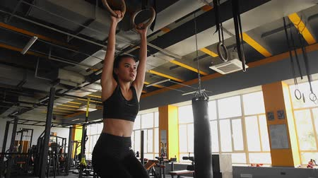 çabaları : Atletic young asian woman is doing legs pull-ups on gymnastic rings in gym, exercises for abs. Sports workout in the gym indoors. Stok Video