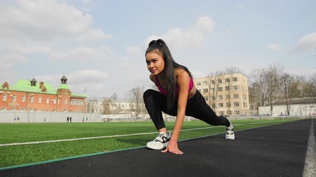 Asian athlete youn girl ready to start on sport stadium.