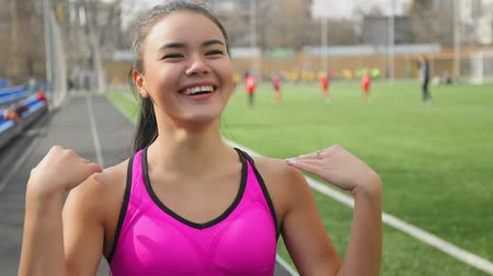 Portrait of asian runner girl laughing on stadium before the start.