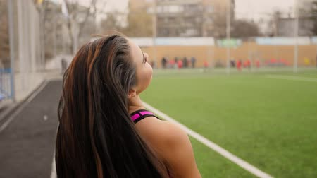 Young sporty asian girl walks at stadium after training and lets her hair down. Stock Footage