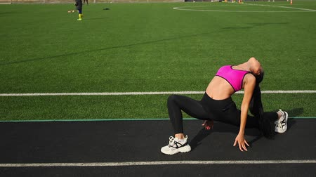 Sporty young asian woman is stretching on the stadium. Sports workout outdoors.
