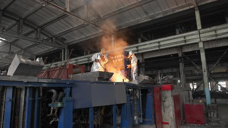 metal casting : Man working with liquid metal in factory. Metal factory sparks