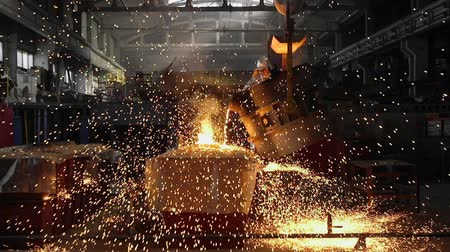 Man working with liquid metal in factory. Metal factory sparks
