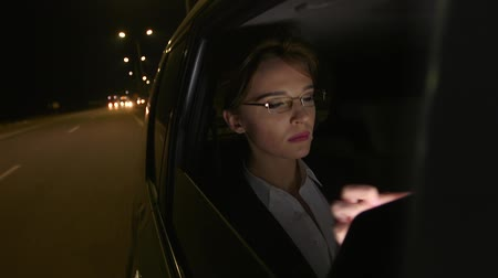 Businesswoman in the car uses a tablet for work. She rides in the car on the night road.