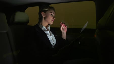 Tired businesswoman in the car talking on the phone. She rides in the car on the night road.