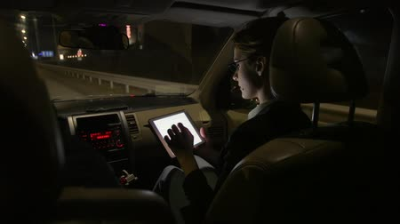 só as mulheres jovens : Businesswoman in the car uses a tablet for work. She rides in the car on the night road.